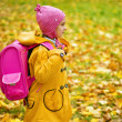 Girl in yellow coat and pink backpack goes to school — Stock Photo #14183985