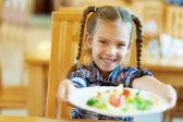 Smiling girl holds out plate of delicious food — Stock Photo