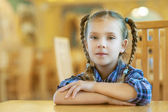Beautiful girl with pigtails sitting on wooden desk — Stock Photo