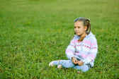 Beautiful girl with pigtails sitting on green grass — Stock Photo