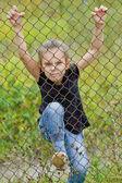 Beautiful girl climbing on a metal grid — Stock Photo