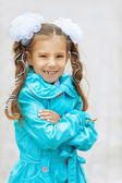 Smiling beautiful girl with bows in blue cloak — Stock Photo