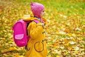 Girl in yellow coat and pink backpack goes to school — Stock Photo
