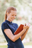 Smiling young woman reading red book — Stock Photo