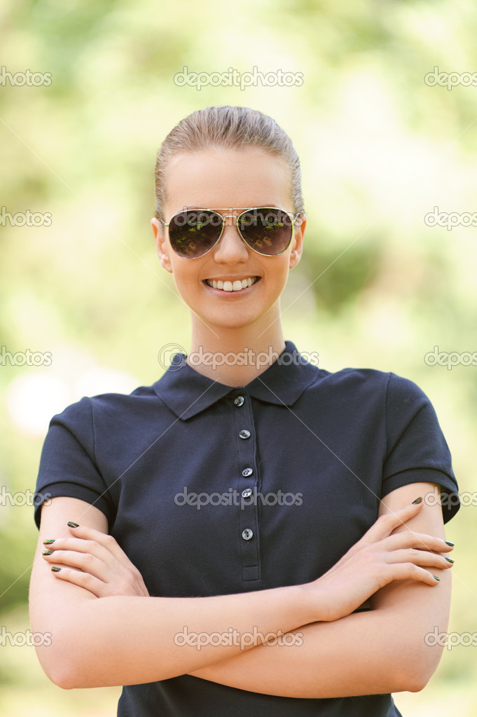 Portrait of beautiful smiling young woman in sunglasses, against background of summer green park. — Stok fotoğraf #14833651