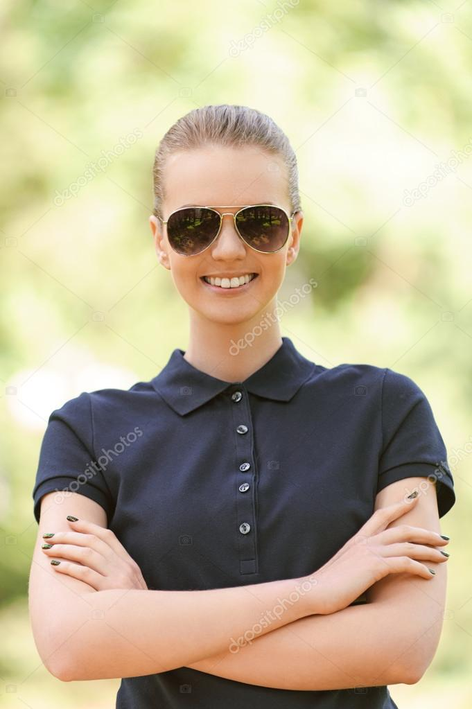 Portrait of beautiful smiling young woman in sunglasses, against background of summer green park. — 图库照片 #14833651