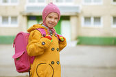 Smiling little girl in yellow coat with pink backpack — Stock Photo