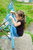 Little girl on old metal simulator — Stock Photo