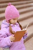 Little girl in pink coat reads book — Stock Photo