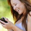 Smiling young woman writing on device — Photo