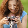 Young woman looking at screen of camera-shot - Photo