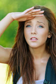 Young woman with hand closes eyes from sun — Stock Photo