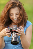 Young woman looking at screen of camera-shot — Stock Photo