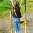 Little girl hanging on old exercise equipment - Foto Stock