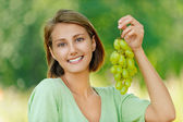 Young woman with bunch of grapes — Stock Photo