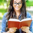 Royalty-Free Stock Photo: Dark-haired young woman reads red book