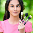 Dark-haired young woman with three makeup brushes — Stock Photo