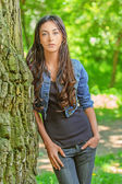 Dark-haired young woman leans on tree — Stock Photo