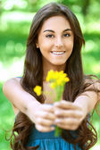 Dark-haired young woman with yellow flowers — Stock Photo