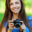 Happy beautiful young woman with camera - Stock Photo