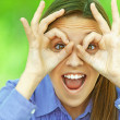 Smiling teenage girl shows glasses out of fingers — ストック写真