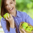 Smiling teenage girl with basket of apples — Stock Photo