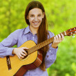 Smiling teenage girl playing guitar - Stock Photo