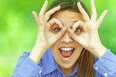 улыбается девушка показывает очки из пальцев — Стоковое фото