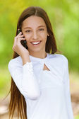 Smiling teenage girl talking on mobile phone — Stock Photo