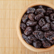 Dried prunes in wooden bowl — Stock Photo #18306601