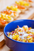 Salad with corn in blue plate — Stock Photo