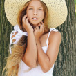 Beautiful smiling girl in hat near large tree — Stock Photo