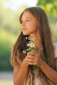 Beautiful girl with camomiles in hands — Stock Photo