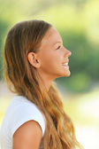 Young beautiful smiling girl in profile — Stock Photo