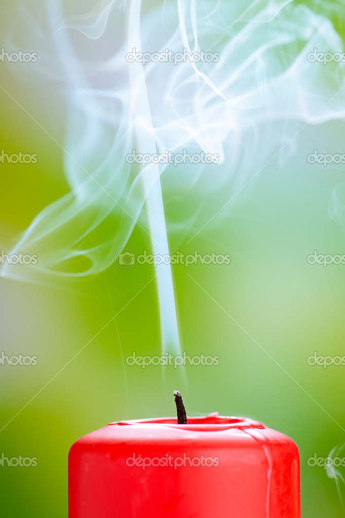 Extinguished red candle with smoke on green background. — Stock Photo #19080145