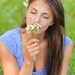 Young woman smelling bouquet of daisies - Stock Photo