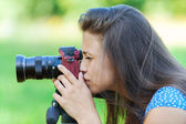Young woman photographed on red camera — Stock Photo