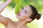 Woman bites off from grape bunches — Stock Photo