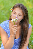 Young woman smelling bouquet of daisies — Stock Photo