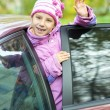 Smiling little girl waving red car - Stock Photo