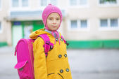 Little girl in yellow coat and pink knapsack — Stock Photo