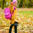 Beautiful girl in yellow jacket and pink knapsack - Stok fotoğraf