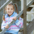 Smiling girl sitting on wooden stairs — Stock Photo