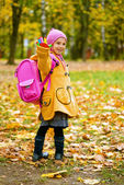 Beautiful girl in yellow jacket and pink knapsack — Stock Photo
