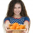 Smiling schoolgirl holds basket of oranges — Stock Photo