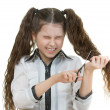 Schoolgirl scissors cuts her hair — Stock Photo