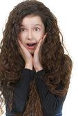 Surprised schoolgirl with dark curly hair — Stock Photo