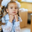 Sad little girl sitting at table — Stockfoto