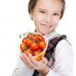 Smiling little girl holding red tomatoes — Stock Photo #21624467