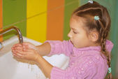 Little girl in pink sweater washes hands — Stock Photo